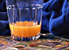 A digital photograph of a glass of orange juice on top of a table covered in comic books
